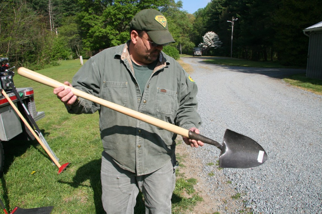 Delaware Forest Service veteran wildland firefighter James Dowd holds a fire shovel and a Pulaski tool, used in wildland firefighting. Volunteer fire companies in Delaware can apply for grants to purchase resources to fight wildfires.